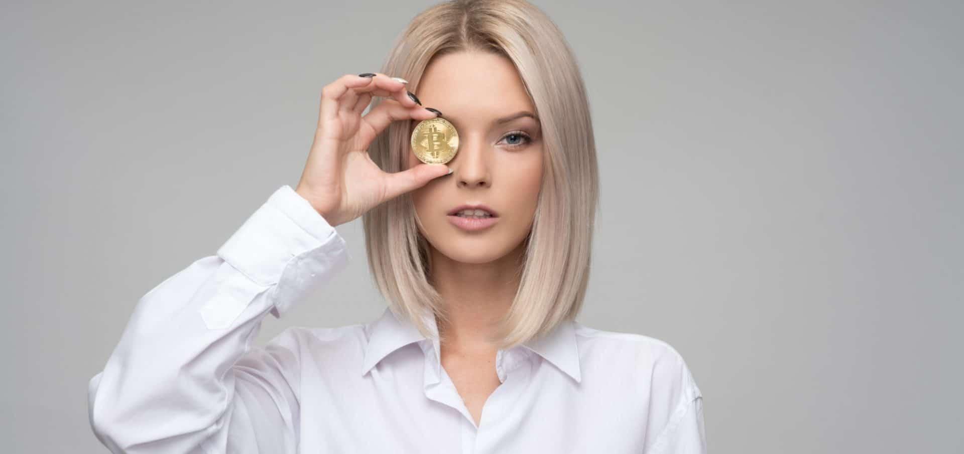 Blonde vrouw met bitcoin voor oog